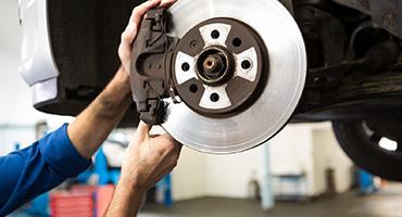 Mécanicien remplace des plaquettes de frein