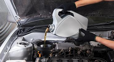 Mécanicien met de l'huile dans le moteur après une vidange